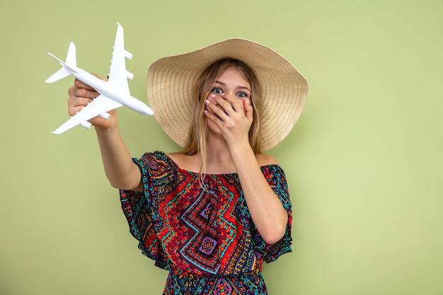 Verrast jong blond slavisch meisje met zonnehoed die hand op haar mond legt en vliegtuigmodel vasthoudt