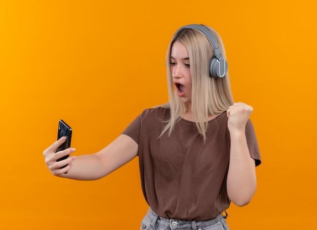 Verrast jong blondemeisje die hoofdtelefoons dragen die mobiele telefoon houden die het met opgeheven vuist op geïsoleerde oranje muur bekijken