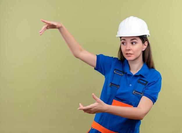 Verrast jong bouwersmeisje met witte veiligheidshelm en blauw uniform beweert iets vast te houden met beide handen op geïsoleerde groene achtergrond met kopie ruimte