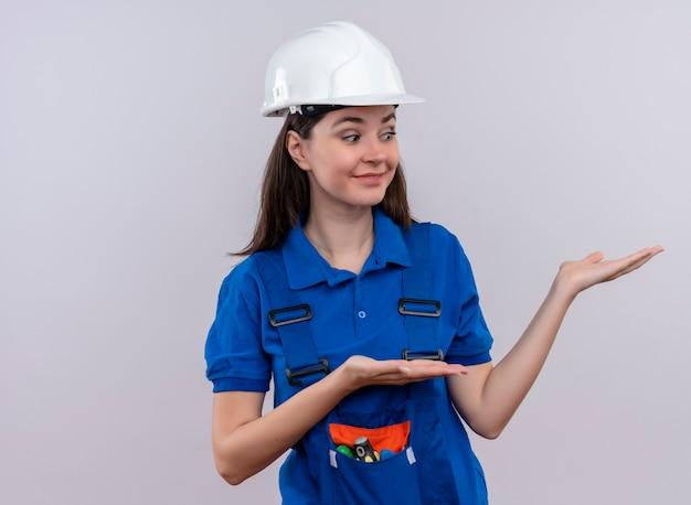 Verrast jong bouwersmeisje met witte veiligheidshelm en blauw uniform houdt handen omhoog op geïsoleerde witte achtergrond met exemplaarruimte