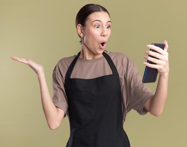Verrast jong brunette kappersmeisje in uniform houdt hand open en kijkt naar telefoon geïsoleerd op olijfgroene muur met kopieerruimte