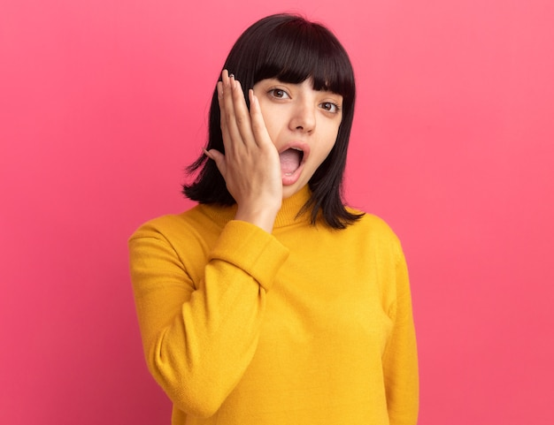 Verrast jong brunette kaukasisch meisje legt hand op gezicht en kijkt naar camera op roze