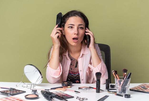Verrast jong brunette meisje zittend aan tafel met make-up tools praten over telefoon haar haren kammen en kijken naar kant geïsoleerd op olijf groene muur met kopie ruimte