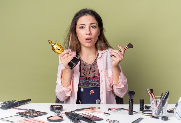 Verrast jong brunette meisje zittend aan tafel met make-uptools met make-upborstel en winnaarbeker geïsoleerd op olijfgroene muur met kopieerruimte