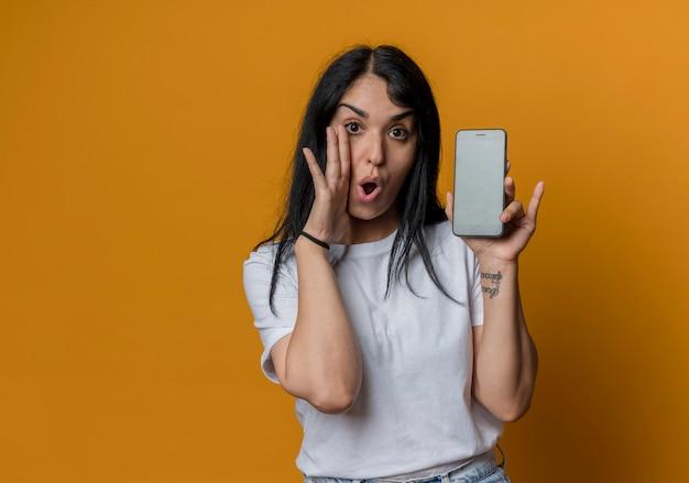 Verrast jong donkerbruin kaukasisch meisje houdt hand dicht bij gezicht en houdt telefoon vast die op oranje muur wordt geïsoleerd