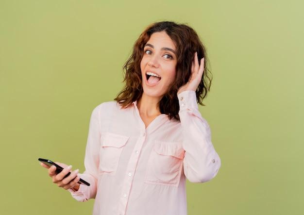 Verrast jong kaukasisch meisje houdt hand achter oor probeert te horen en houdt telefoon geïsoleerd op groene achtergrond met kopie ruimte
