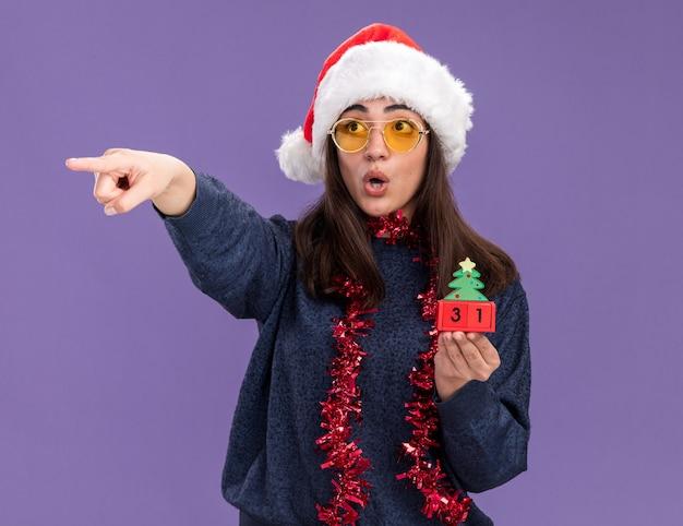 Verrast jong kaukasisch meisje in zonnebril met kerstmuts en slinger om de nek houdt kerstboomversiering en wijst aan de zijkant geïsoleerd op paarse muur met kopieerruimte
