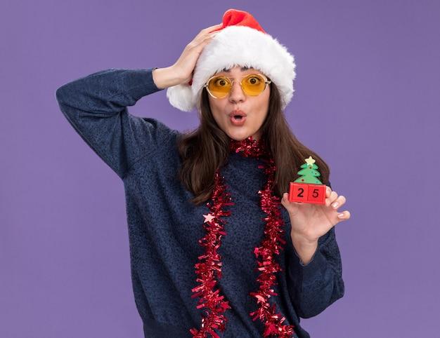 Verrast jong kaukasisch meisje in zonnebril met kerstmuts en slinger om nek houdt kerstboom ornament en legt hand op hoofd geïsoleerd op paarse muur met kopie ruimte