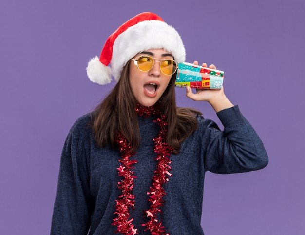 Verrast jong kaukasisch meisje in zonnebril met kerstmuts en slinger om nek houdt papieren beker dicht bij oor en kijkt naar kant geïsoleerd op paarse muur met kopieerruimte