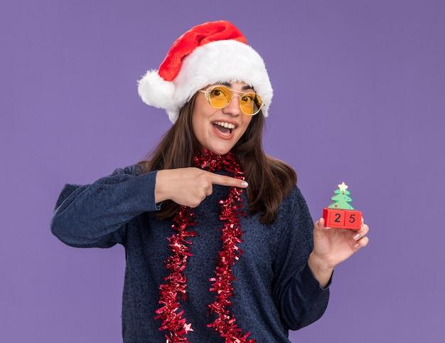 Verrast jong kaukasisch meisje in zonnebril met kerstmuts en slinger om nek houdt vast en wijst naar kerstboomversiering geïsoleerd op paarse muur met kopieerruimte