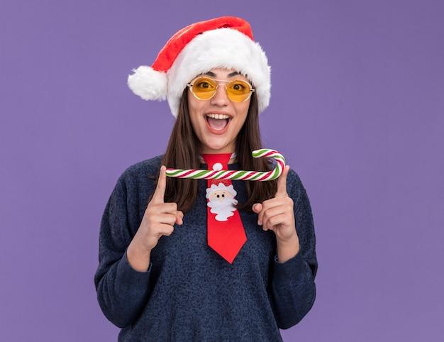 Verrast jong kaukasisch meisje in zonnebril met kerstmuts en stropdas santa bedrijf candy cane geïsoleerd op paarse achtergrond met kopie ruimte