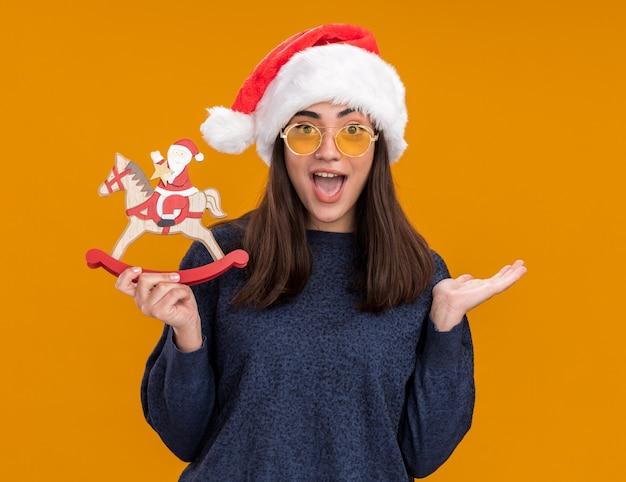 Verrast jong kaukasisch meisje in zonnebril met kerstmuts houdt santa op schommelpaarddecoratie en houdt hand open geïsoleerd op oranje muur met kopieerruimte