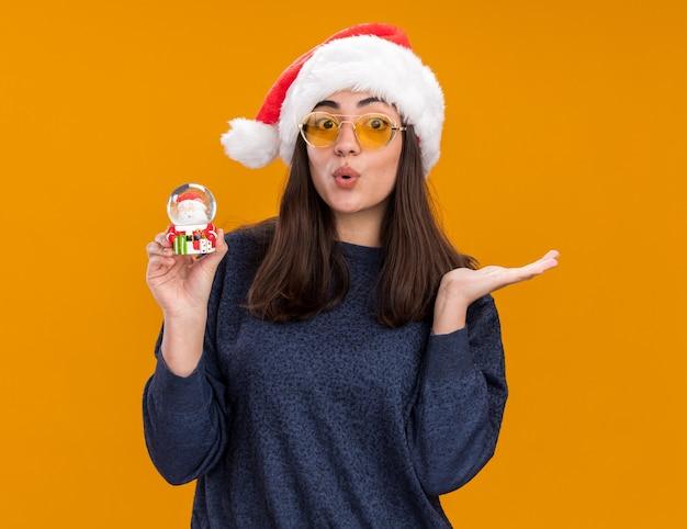 Verrast jong kaukasisch meisje in zonnebril met kerstmuts houdt sneeuwbol vast en houdt hand open geïsoleerd op oranje muur met kopieerruimte