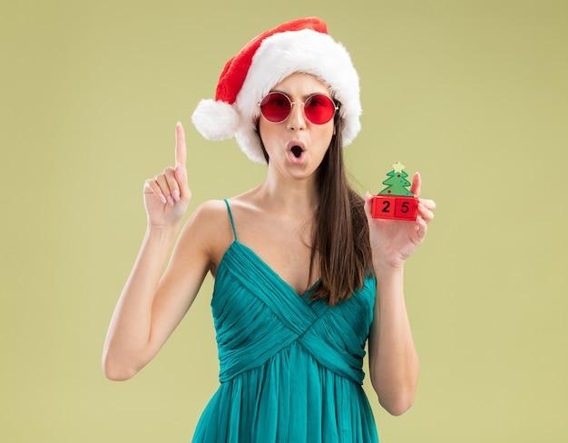 Verrast jong kaukasisch meisje in zonnebril met kerstmuts kerstboom ornament te houden en omhoog te wijzen