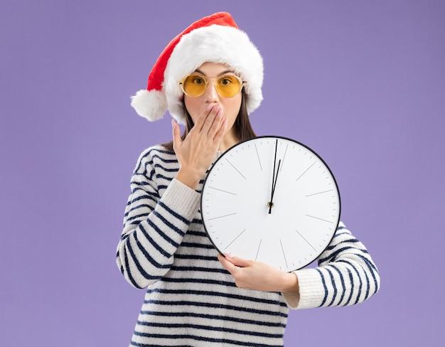 Verrast jong kaukasisch meisje in zonnebril met kerstmuts legt hand op mond en houdt klok