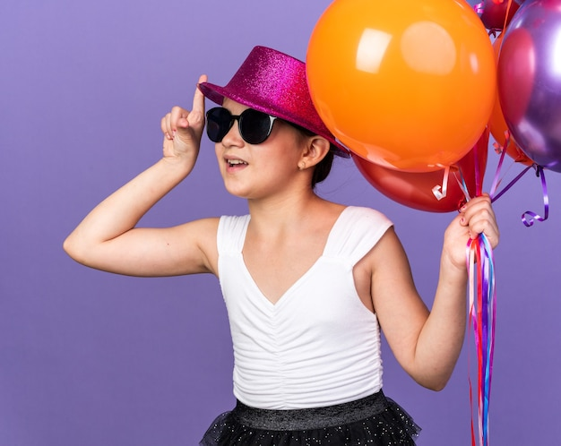 Verrast jong kaukasisch meisje in zonnebril met violette feestmuts met helium ballonnen en omhoog geïsoleerd op paarse muur met kopie ruimte