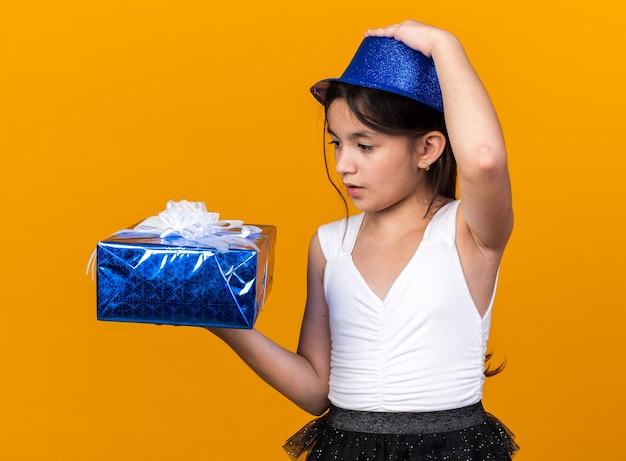 Verrast jong kaukasisch meisje met blauwe feestmuts hand zetten hoed en kijken naar geschenkdoos geïsoleerd op oranje muur met kopie ruimte