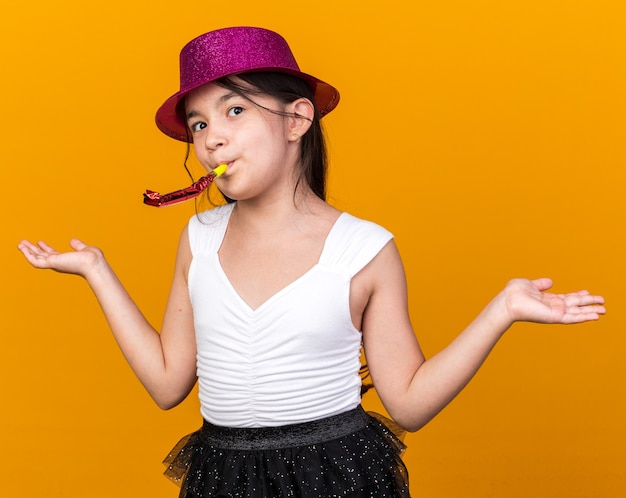 Verrast jong kaukasisch meisje met paarse feestmuts blazend feestfluitje dat handen open houdt geïsoleerd op oranje muur met kopieerruimte