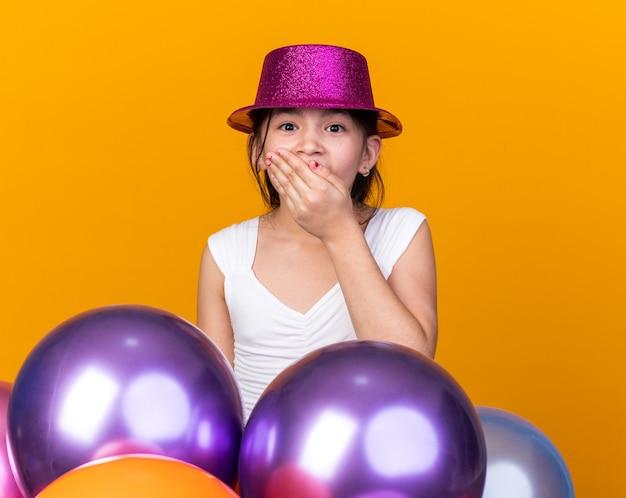 Verrast jong kaukasisch meisje met paarse feestmuts hand op mond staande met helium ballonnen geïsoleerd op oranje muur met kopie ruimte