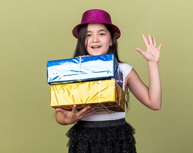 Verrast jong kaukasisch meisje met paarse feestmuts met geschenkdozen en staande met opgeheven hand geïsoleerd op olijfgroene muur met kopieerruimte