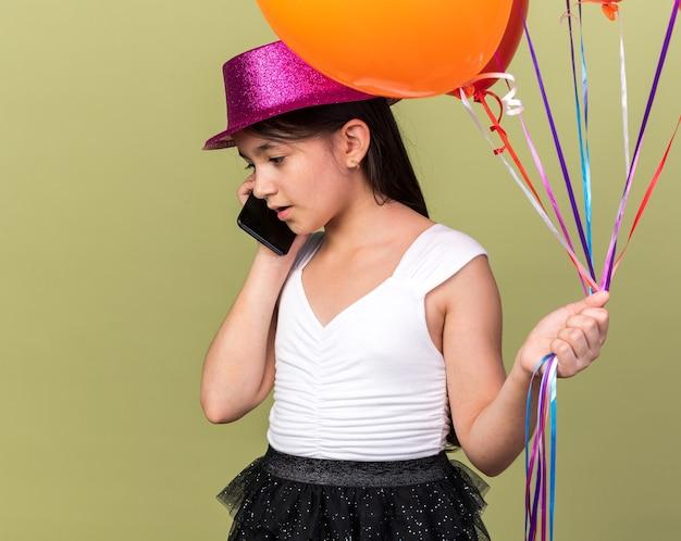 Verrast jong kaukasisch meisje met paarse feestmuts met helium ballonnen praten over telefoon geïsoleerd op olijfgroene muur met kopie ruimte