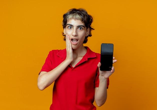 Verrast jong kaukasisch meisje met pixiekapsel die mobiele telefoon houden en hand op wang zetten die op oranje achtergrond met exemplaarruimte wordt geïsoleerd