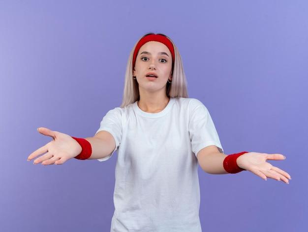Verrast jong kaukasisch sportief meisje met beugels die hoofdband dragen