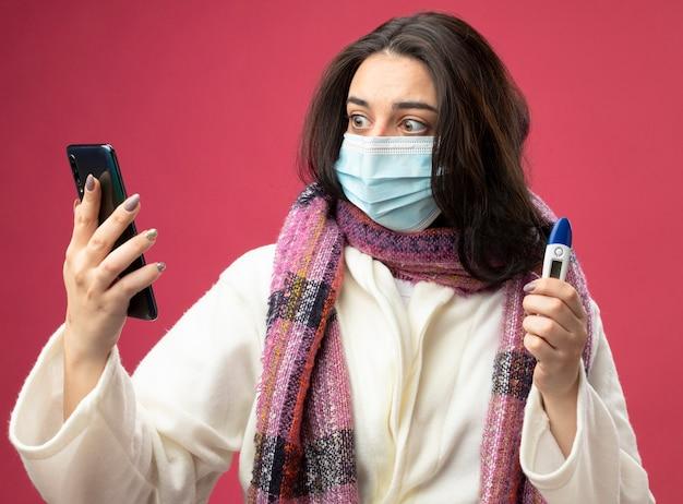 Verrast jong kaukasisch ziek meisje dat een gewaad en een sjaal met een masker draagt en een mobiele telefoon en een thermometer houdt die naar de telefoon kijkt die op een karmozijnrode muur wordt geïsoleerd