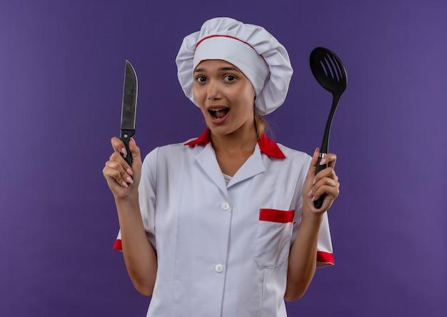 Verrast jong kokwijfje die de pollepel en het mes van de chef-kok eenvormige holding op geïsoleerde achtergrond met exemplaarruimte dragen