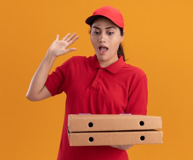 Verrast jong leveringsmeisje die eenvormig en glb dragen die en pizzadozen houden die hand opheffen die op oranje muur wordt geïsoleerd
