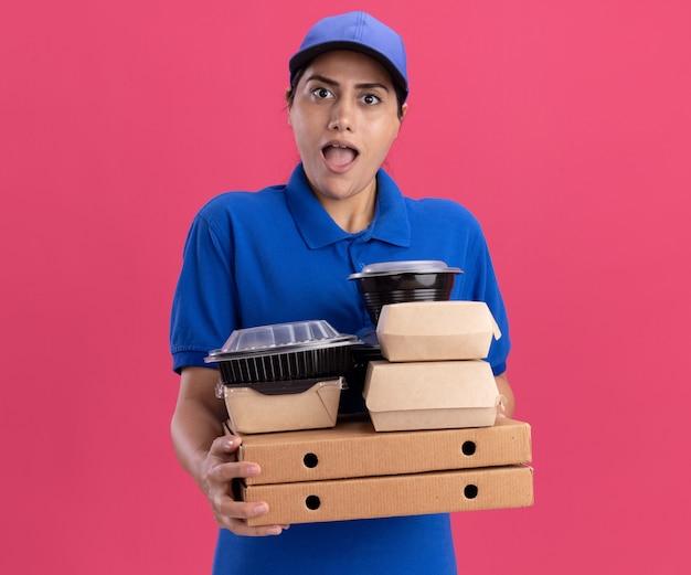 Verrast jong leveringsmeisje die eenvormig met glb dragen die voedselcontainers op pizzadozen houden die op roze muur worden geïsoleerd