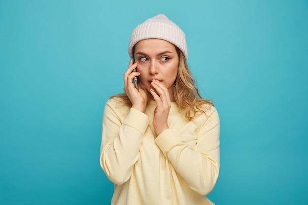 Verrast jong meisje dat de winterhoed draagt die over telefoon spreekt die kant bekijkt die hand op mond houdt