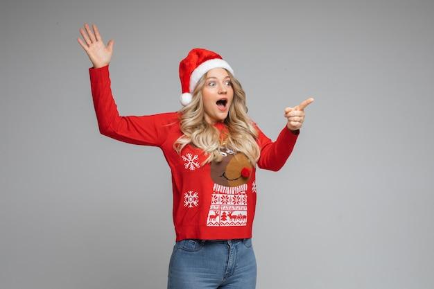 Verrast jong meisje in kerstmuts en rode warme wintertrui wijs opzij met de vinger op een grijze achtergrond met kopieerruimte