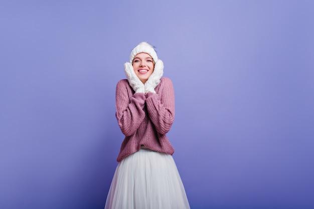 Verrast jong meisje in winterkleding verbazing uiten. kaukasisch vrouwelijk model met geschokte gezichtsuitdrukking.