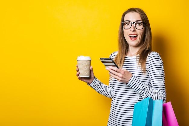 Verrast jong meisje kijkt naar de telefoon, met een papieren beker met koffie en met boodschappentassen op een gele achtergrond