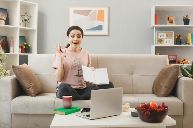 Verrast jong meisje met notitieboekje zittend op de bank achter de salontafel en kijkt naar laptop in de woonkamer