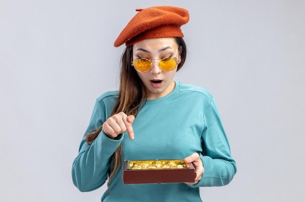 Verrast jong meisje op valentijnsdag met een hoed met een bril die vasthoudt en wijst op een doos snoepjes geïsoleerd op een witte achtergrond