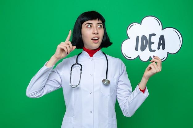Verrast jong, mooi kaukasisch meisje in doktersuniform met een stethoscoop die naar boven wijst en een ideebel vasthoudt