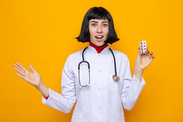 Verrast jong, mooi kaukasisch meisje in doktersuniform met stethoscoop die pilverpakking vasthoudt en hand open houdt