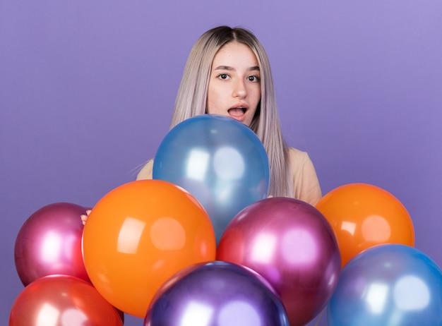 Verrast jong mooi meisje dat achter ballonnen staat