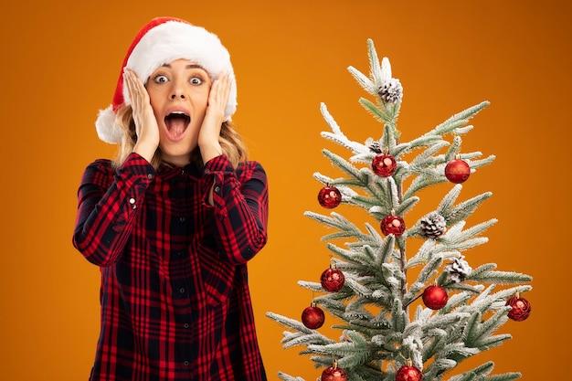 Verrast jong mooi meisje dat in de buurt van de kerstboom staat en een kerstmuts draagt die handen op de wangen legt, geïsoleerd op een oranje achtergrond