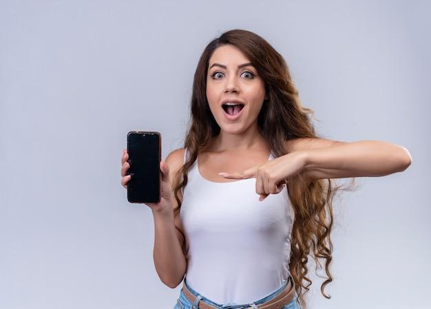 Verrast jong mooi meisje dat mobiele telefoon houdt en op geïsoleerde oranje muur met exemplaarruimte richt