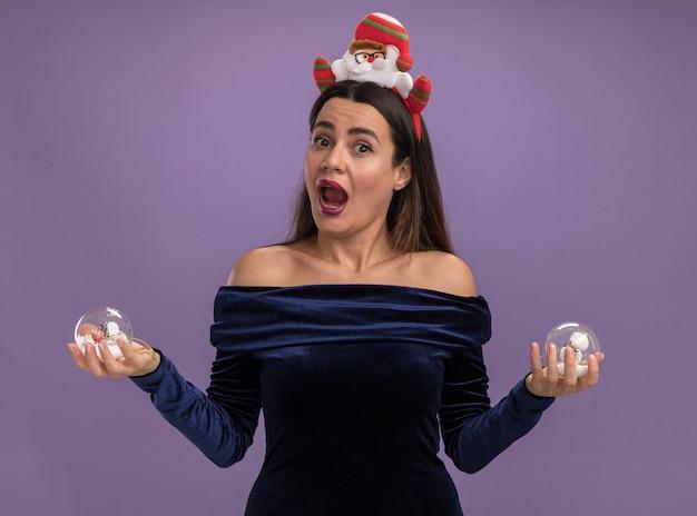 Verrast jong mooi meisje draagt blauwe jurk en kerst haar hoepel met kerstballen geïsoleerd op paarse achtergrond