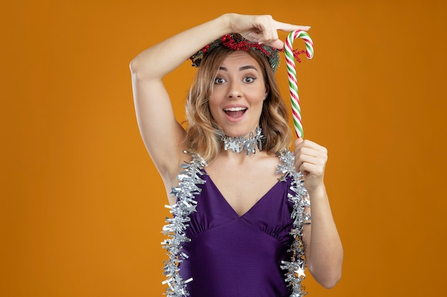 Verrast jong mooi meisje draagt paarse jurk met krans met guirlande op nek met kerstsnoep geïsoleerd op bruine achtergrond
