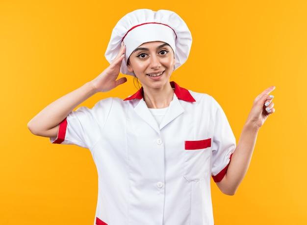 Verrast jong mooi meisje in uniform van de chef-kok wijst aan de zijkant