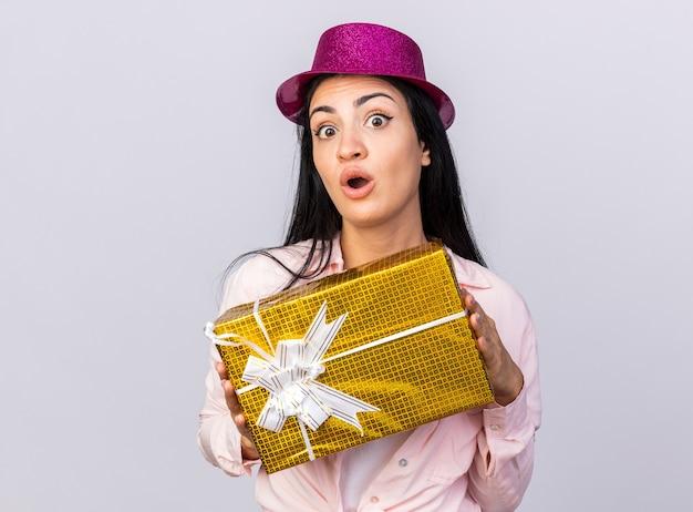 Verrast jong mooi meisje met een feesthoed die een geschenkdoos op de camera vasthoudt