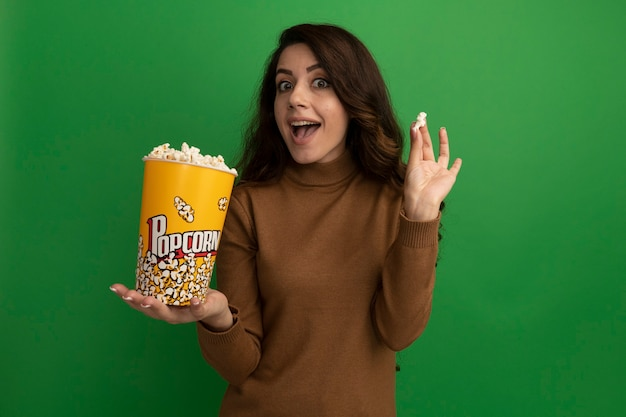 Verrast jong mooi meisje met emmer popcorn met popcorn vrede geïsoleerd op groene muur