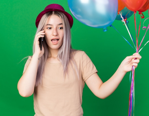 Verrast jong mooi meisje met feestmuts en beugels met ballonnen spreekt op de telefoon