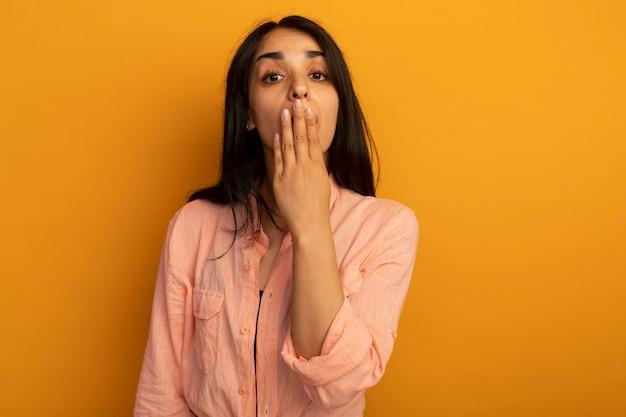 Verrast jong mooi meisje met roze t-shirt bedekte mond met hand geïsoleerd op geel met kopie ruimte