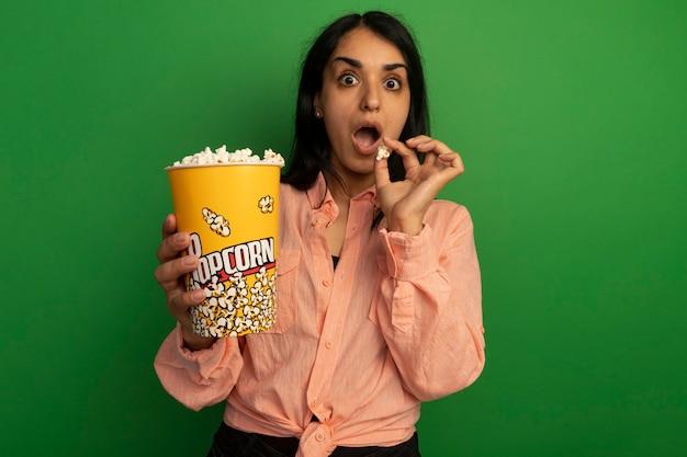 Verrast jong mooi meisje met roze t-shirt met emmer popcorn geïsoleerd op groene muur